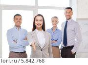 Женщина-руководитель протягивает руку для рукопожатия, стоя со своими коллегами в офисе. Стоковое фото, фотограф Syda Productions / Фотобанк Лори