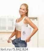 Купить «Очаровательная девушка с весами в руках показывает, как она похудела, оттянув пояс джинсов», фото № 5842824, снято 23 марта 2013 г. (c) Syda Productions / Фотобанк Лори