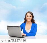 Купить «Дружелюбная девушка в голубом джемпере приветливо улыбается, сидя перед ноутбуком», фото № 5857416, снято 22 сентября 2013 г. (c) Syda Productions / Фотобанк Лори