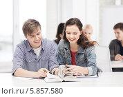 Молодой человек и девушка читают учебник, сидя за партой в классе. Стоковое фото, фотограф Syda Productions / Фотобанк Лори
