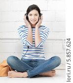 Купить «Счастливая девушка в полосатом джемпере и в джинсах слушает музыку в наушниках, сидя на полу, скрестив ноги», фото № 5857624, снято 31 марта 2012 г. (c) Syda Productions / Фотобанк Лори