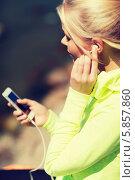Купить «Девушка занимается спортом и слушает музыку через наушники смартфона», фото № 5857860, снято 19 июня 2013 г. (c) Syda Productions / Фотобанк Лори