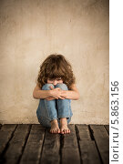 Портрет грустной девочки, сидящей у стены. Стоковое фото, фотограф yarruta / Фотобанк Лори