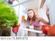 Купить «Беременная женщина заглядывает в холодильник, полный здоровой еды», фото № 5869672, снято 30 апреля 2014 г. (c) Анатолий Типляшин / Фотобанк Лори