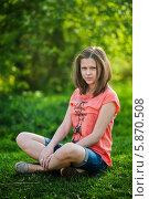 Купить «Молодая девушка сидит на траве сложив ноги под себя», эксклюзивное фото № 5870508, снято 1 мая 2014 г. (c) Игорь Низов / Фотобанк Лори