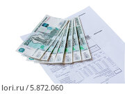Купить «Бумажные купюры и квитанция на оплату коммунальных услуг на белом фоне», фото № 5872060, снято 19 апреля 2018 г. (c) Александр Самолетов / Фотобанк Лори