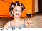 Красивая домохозяйка с бигудями держит бокал красного вина в руке на кухне. Стоковое фото, фотограф Андрей Затулло / Фотобанк Лори