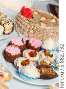 Торт с кремом и пирожные с кремом, фруктами и сахарной пудрой на тарелках на столе. Стоковое фото, фотограф Андрей Затулло / Фотобанк Лори