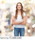 Купить «Девушка в белой футболке и в джинсах стоит, скрестив руки», фото № 5888640, снято 26 февраля 2014 г. (c) Syda Productions / Фотобанк Лори