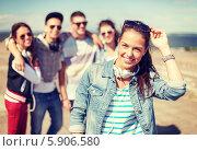 Купить «Компания веселых друзей стоит позади радостной девушки в джинсовой куртке», фото № 5906580, снято 20 июля 2013 г. (c) Syda Productions / Фотобанк Лори
