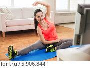 Девушка в красной футболке выполняет физические упражнения, сидя дома перед телевизором на коврике для фитнеса. Стоковое фото, фотограф Syda Productions / Фотобанк Лори