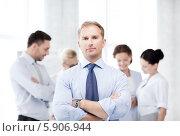 Купить «Уверенный бизнесмен стоит, скрестив руки, на фоне сотрудников офиса», фото № 5906944, снято 9 июня 2013 г. (c) Syda Productions / Фотобанк Лори