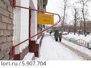 """Купить «Откидное предупреждение """"Опасная зона"""" на фасаде жилого дома. Вдалеке идут женщина с ребенком», эксклюзивное фото № 5907704, снято 6 января 2013 г. (c) Родион Власов / Фотобанк Лори"""