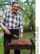 Купить «Счастливый пожилой мужчина готовит мясо на мангале на даче», эксклюзивное фото № 5912900, снято 13 мая 2014 г. (c) Яна Королёва / Фотобанк Лори