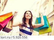 Купить «Красивая девушка радуется удачному шопингу, подняв вверх руки с разноцветными пакетами», фото № 5920556, снято 29 июня 2013 г. (c) Syda Productions / Фотобанк Лори