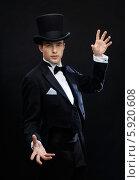 Купить «Фокусник в черной шляпе на черном фоне», фото № 5920608, снято 12 сентября 2013 г. (c) Syda Productions / Фотобанк Лори