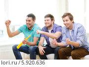 Купить «Трое друзей с азартом смотрят спортивную передачу, сидя на диване перед телевизором», фото № 5920636, снято 22 марта 2014 г. (c) Syda Productions / Фотобанк Лори
