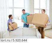 Друзья с большими картонными коробками собираются переезжать в новую квартиру. Стоковое фото, фотограф Syda Productions / Фотобанк Лори
