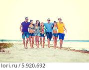 Купить «Летний отдых. Счастливая компания молодых людей идет, обнявшись, по берегу», фото № 5920692, снято 31 августа 2013 г. (c) Syda Productions / Фотобанк Лори