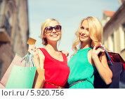 Две девушки с пакетами и кредитной картой наслаждаются процессом шопинга. Стоковое фото, фотограф Syda Productions / Фотобанк Лори