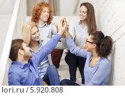 Купить «Дружный творческий коллектив на лестнице современного офиса, руки сложили вместе», фото № 5920808, снято 1 февраля 2014 г. (c) Syda Productions / Фотобанк Лори