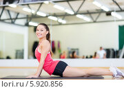 Купить «Молодая привлекательная женщина занимается в спортивном зале, выполняя упражнения, лежа на специальном коврике», фото № 5920856, снято 28 сентября 2013 г. (c) Syda Productions / Фотобанк Лори