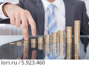 Купить «бизнесмен поднимается по лестнице из монет», фото № 5923460, снято 29 декабря 2013 г. (c) Андрей Попов / Фотобанк Лори