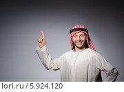 Купить «Улыбающийся арабский мужчина в белой тунике и яркой арафатке указывает пальцем наверх», фото № 5924120, снято 17 декабря 2013 г. (c) Elnur / Фотобанк Лори