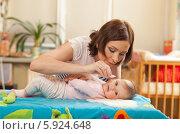 Мама закапывает ребенку в нос средство от насморка. Стоковое фото, агентство BE&W Photo / Фотобанк Лори