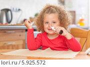 Маленькая кудрявая девочка сама закапывает в нос средство от насморка. Стоковое фото, агентство BE&W Photo / Фотобанк Лори