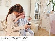 Мать уговаривает капризного малыша принять лекарство в сиропе. Редакционное фото, агентство BE&W Photo / Фотобанк Лори