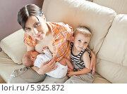 Купить «Мама кормит ребенка грудью, а страший сын сидит рядом», фото № 5925872, снято 21 ноября 2019 г. (c) BE&W Photo / Фотобанк Лори