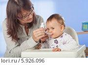 Женщина дает ребенку лекарство в мерной ложке. Стоковое фото, агентство BE&W Photo / Фотобанк Лори