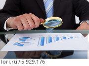 Купить «бизнесмен смотрит на график через лупу», фото № 5929176, снято 21 февраля 2014 г. (c) Андрей Попов / Фотобанк Лори