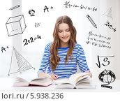 Купить «Подготовка к экзаменам. Девушка в полосатой футболке сидит за столом с учебниками на фоне стены с чертежами и формулами», фото № 5938236, снято 26 февраля 2014 г. (c) Syda Productions / Фотобанк Лори