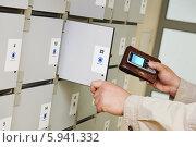 Купить «Человек кладёт бумажник и телефон в ячейку для хранения», фото № 5941332, снято 8 мая 2014 г. (c) Дмитрий Калиновский / Фотобанк Лори