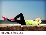 Девушка на улице выполняет спортивные упражнения, лежа на специальном коврике для фитнеса. Стоковое фото, фотограф Syda Productions / Фотобанк Лори