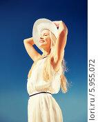 Купить «Красивая девушка в белом платье придерживает руками шляпу на фоне голубого неба», фото № 5955072, снято 19 июня 2013 г. (c) Syda Productions / Фотобанк Лори