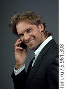 Привлекательный молодой мужчина в темном костюме разговаривает по телефону и улыбается. Стоковое фото, агентство BE&W Photo / Фотобанк Лори