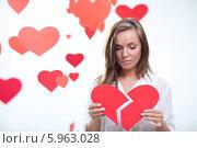 Купить «Девушка держит разорванное красное сердечко», фото № 5963028, снято 8 декабря 2013 г. (c) Raev Denis / Фотобанк Лори
