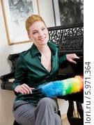 Купить «Очаровательная блондинка в зеленой блузке с метелкой для вытирания пыли сидит у рояля», фото № 5971364, снято 17 октября 2018 г. (c) BE&W Photo / Фотобанк Лори