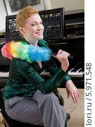 Купить «Очаровательная блондинка в зеленой блузке с метелкой для вытирания пыли сидит у рояля», фото № 5971548, снято 17 октября 2018 г. (c) BE&W Photo / Фотобанк Лори
