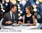 Купить «Романтический вечер в ресторане. Мужчина и женщина сидят за сервированным столиком», фото № 5972256, снято 9 марта 2014 г. (c) Syda Productions / Фотобанк Лори