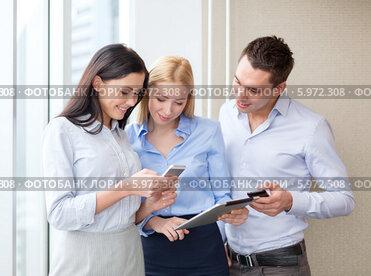 Коллеги в офисе общаются, просматривая новости на экране смартфона и планшетного компьютера