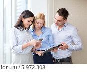 Купить «Коллеги в офисе общаются, просматривая новости на экране смартфона и планшетного компьютера», фото № 5972308, снято 23 ноября 2013 г. (c) Syda Productions / Фотобанк Лори