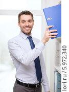 Купить «Молодой бизнесмен достает папку с полки в офисе», фото № 5972340, снято 15 марта 2014 г. (c) Syda Productions / Фотобанк Лори