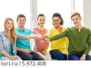Купить «Счастливые друзья сидят на подоконнике и сложили руки вместе», фото № 5972408, снято 29 марта 2014 г. (c) Syda Productions / Фотобанк Лори