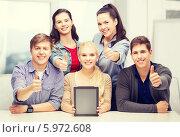 Купить «Группа жизнерадостных молодых людей с планшетным компьютером показывает жест одобрения», фото № 5972608, снято 2 ноября 2013 г. (c) Syda Productions / Фотобанк Лори