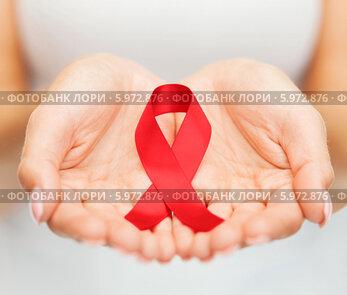 Красная лента- символ борьбы против СПИДа в женских ладонях