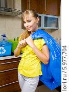 Купить «Симпатичная девушка выносит с кухни большой мешок с мусором», фото № 5977704, снято 20 июля 2018 г. (c) BE&W Photo / Фотобанк Лори